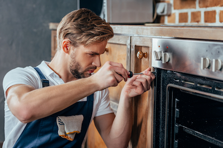 image of an appliance engineer fixing an oven